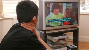 A hard of hearing boy with a hearing aid watches TV with the help of the RNID loop system. From the Solutions Catalogue 2008.